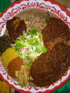 A base of Injera with side dishes on top to rip and dip.